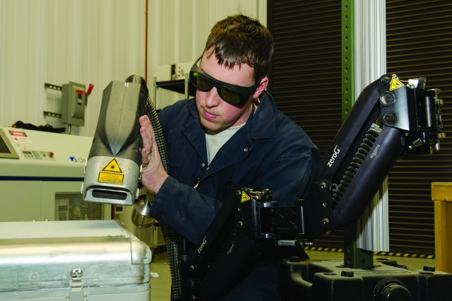 Jonathan Grebb, a sandblaster at Tobyhanna Army Depot, Pa., uses a laser paint stripper on an unmanned threat emitter box, with help from the zeroG Mechanical Arm.