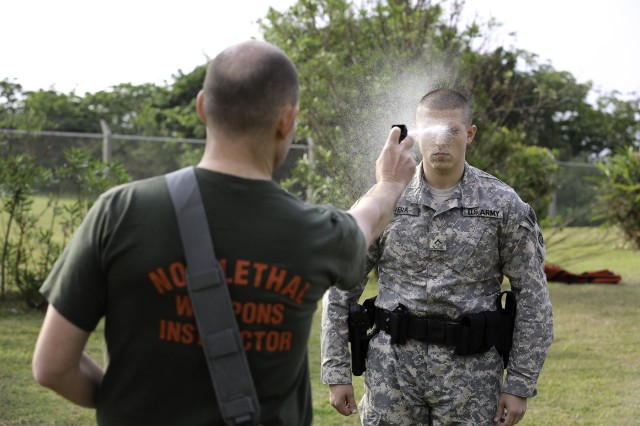 Sgt. 1st Class Mark Davis, Provost Sergeant, sprays a new MP in the face with Oleoresin Capsicum Dec. 29 at Torii Station.