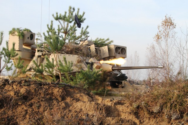 From a hasty fighting position, U.S. Soldiers fire a M240C coaxial machine gun from a Bradley Fighting Vehicle, Nov. 5, in Pabrade, Lithuania - to repel an advance of British forces during a situational training exercise. The training is part of the multinational exercise Iron Sword 2014 involving 2,500 Soldiers from Canada, the Czech Republic, Estonia, Germany, Hungary, Lithuania, Luxembourg, the United States and the United Kingdom.