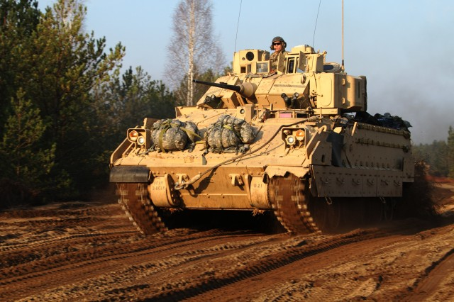 First Lt. John O'Brien, platoon leader, B Company, 2nd Battalion, 8th Cavalry Regiment, 1st Brigade Combat Team, 1st Cavalry Division, guides his platoon from the turret of a Bradley Fighting Vehicle as the convoy of Bradleys and Strykers moves towards its objective, Nov. 11 during Iron Sword 2014, a multinational combined arms exercise hosted by the Lithuanian Land Forces and involving nearly 2,500 soldiers from nine NATO nations.
