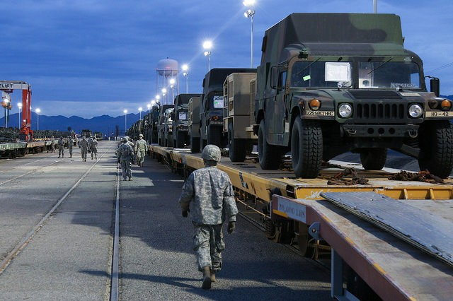 """Soldiers from 1st Striker Brigade Combat Team, """"Arctic Wolves"""", transport over 600 vehicles from the rail yard in preparation for their deployment validation at the National Training Center at Fort Irwin, Calif., Jan 10. The decisive-action rotation is designed to test and validate the Alaska brigade's full spectrum capacity to conduct a wide variety of mission sets. (U.S. Army photo by Sgt. Christopher Prows, 5th Mobile Public Affairs Detachment)"""