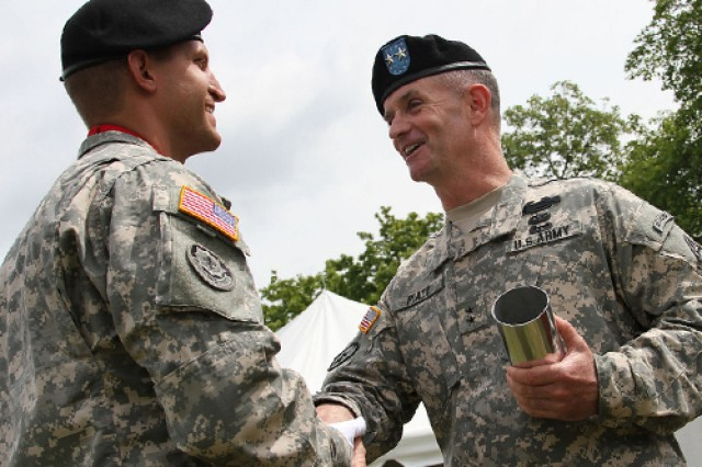 GRAFENWOEHR, Germany -- Maj. Gen. Walter E. Piatt gives a command coin to 1st Lt. John M. Wasniewski of Battery C, 2nd Cavalry Regiment, after accepting the inscribed canister representing the last round of the honors fired from the 13-gun salute. Piatt handed over command resposibility of the 7th Army Joint Multinational Training Command to Brig. Gen. Christopher G. Cavoli at Tower Barracks parade field July 21, 2014.