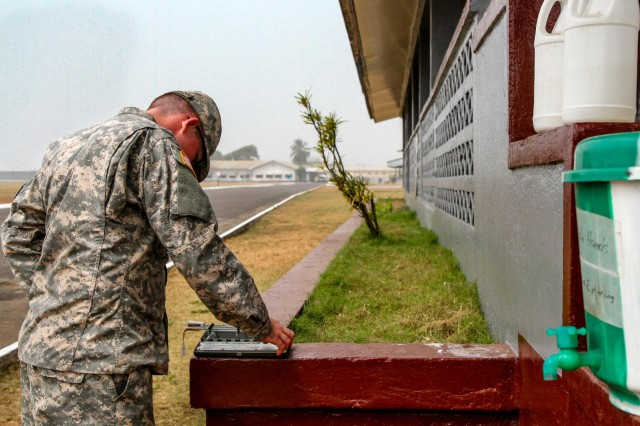 Spc. William Ferguson, native of Oklahoma City, health specialist for Headquarters Support Company, Headquarters and Headquarters Battalion, performs his routine check of the Heat Category wet-bulb thermometer, outside the Barclay Training Center medical building, Monrovia, Liberia, Jan. 12, 2015. Every hour Ferguson checks the temperature on camp to help prevent Soldier heat casualties, refills the bleach buckets and helps maintain the overall health of his fellow Soldiers while deployed for Operation United Assistance. Operation United Assistance is a Department of Defense operation in Liberia to provide logistics, training and engineering support to U.S. Agency for International Development-led efforts to contain the Ebola virus outbreak in western Africa.