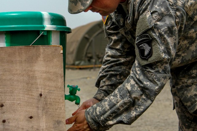 Capt. Austin Duckwiler, native of Davenport, Iowa, department joint automations management officer, Signal Company, Headquarters and Headquarters Battalion, 101st Airborne Division (Air Assault), washes his hands thoroughly with a bleach-water solution before entering the dining facility at Barclay Training Center, Monrovia, Liberia, Jan. 13, 2015. Buckets filled with a bleach-water solution are stationed outside of camp facilities with a higher personnel traffic volume to promote hand washing and prevent spread of any possible bacterial transmissions. Operation United Assistance is a Department of Defense operation in Liberia to provide logistics, training and engineering support to U.S. Agency for International Development-led efforts to contain the Ebola virus outbreak in western Africa.