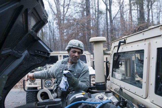 U.S. Army Reserve Master Sgt. Willie Atkinson with the 412th Theater Engineer Command's Deployable Command Post One, checks the oil level on his up-armored Humvee before convoying to set up a tactical operations center and train on the tele-engineering kit during battle assembly in Vicksburg, Miss., Jan. 11. The tele-engineering kit allows radio, video, internet and phone capabilities in an austere environment. (U.S. Army photo by Staff Sgt. Roger Ashley)