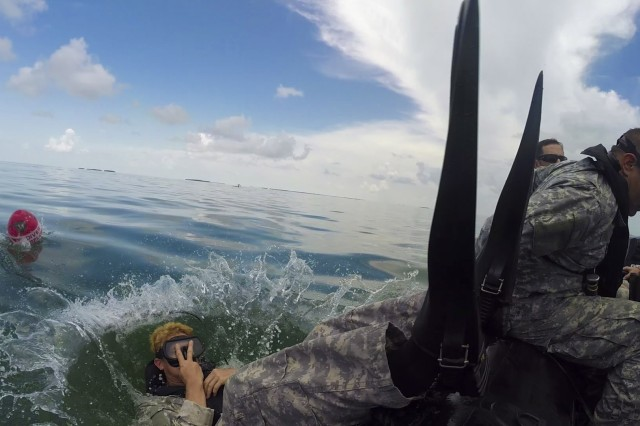 A Soldier from 20th Special Forces Group, Army National Guard, performs a back roll entry into the water during training and recertification at the U.S. Army Special Forces Underwater Operations School, June 22, 2014 in Key West, Fl. Even after their initial training to be part of Special Forces, known as Green Berets, must continue to attend schools and train just to maintain proficiency in their specialty skill sets, like combat diver.