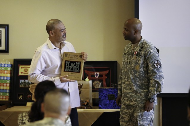 Mr. Charles Transley, Director of Public Works, U.S. Army Garrison - Okinawa, presents Command Sgt. Maj. Antez Gilbert a commemorative plaque Jan. 9 at the senior enlisted leader's farewell at Torii Station, Okinawa.
