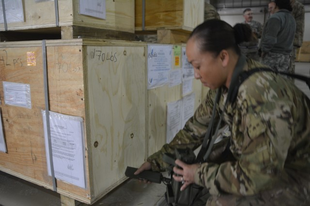 Sgt. 1st Class Teng Xiong-White, 4th Resolute Support Sustainment Brigade radiation safety officer, checks containers for radiation leakage before  shipping equipment that uses tritium as a constant light source to the Army Dosimetry Center at Redstone Arsenal, Ala.
