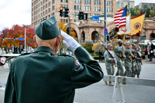 Retired Army 1st Sgt. William Staude, of Elliott, Pa., salutes soldiers from the 316th Expeditionary Sustainment Command, stationed in Coraopolis, Pa., as they march past him during the Veterans Day parade in downtown Pittsburgh, Nov. 11.