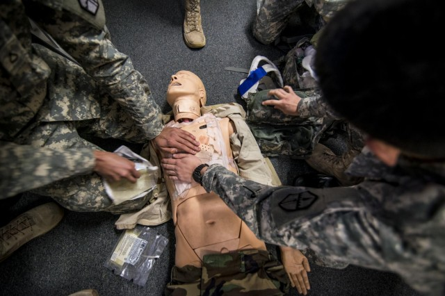 A team of Army medic students work to stabilize a dummy with gunshot wounds during a simulated scenario at an 18-day Sapper Advanced Tactical Medical Course taught by the 321st Engineer Battalion at Gowen Field Air National Guard Base, Idaho, in January, 2015. (U.S. Army photo by Sgt. 1st Class Michel Sauret)