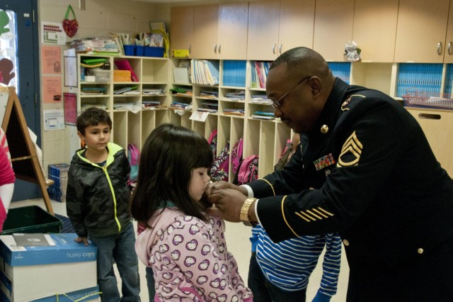 U.S. Army Reserve Sgt. 1st Class Darren Mitchell, operations noncommissioned officer with the 412th Theater Engineer Command, pins a 412th TEC pin on Amora McDiffett, 7, at Pelahatchie Elementary School during a visit to the school to recognize her Jan. 21. Mitchell received a construction paper flag created by Amora on Veterans Day and wanted to recognize her for her support. (U.S. Army photo by Staff Sgt. Debralee Best)
