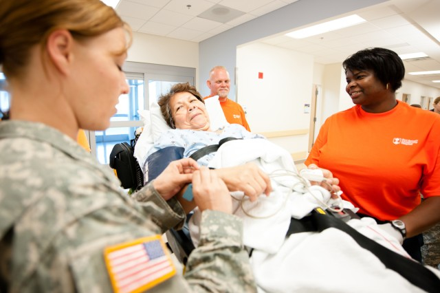 E.J. Carter, the first patient at Fort Belvoir Community Hospital, smiles at staff members upon arriving at the new hospital from DeWitt Army Community Hospital, Aug. 31, 2011. The new state-of-the-art hospital was built through the U.S. Army Corps of Engineers.