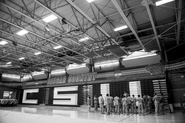 Approximately 20 U.S. Army Soldiers gather inside a gymnasium to prepare for the arrival of 100 Chicago youths who grew up in a single-parent household before the start of the Steve Harvey Mentoring Weekend hosted at Chicago State University during Jan. 23-25. (U.S. Army photo by Sgt. 1st Class Michel Sauret)