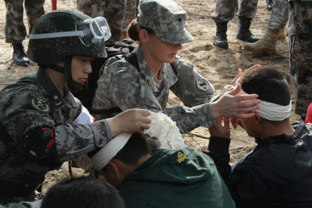 Spc. Bobbi Sue Sanders and her Chinese counterpart deliver immediate care to volunteer patients during the 2015 China Disaster Management Exchange practical field exchange, Jan. 18, 2015.