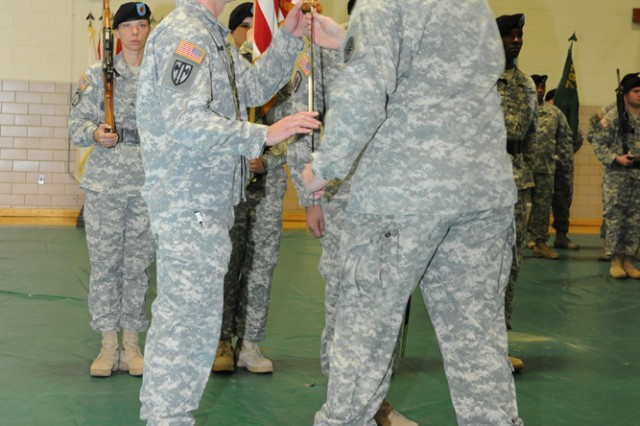 Command Sgt. Maj. David Tookmanian, left, 14th Military Police Brigade command sergeant major, accepts the Noncommissioned Officer's Sword from Col. Bryan Patridge, 14th MP Brigade commander, during an assumption of responsibility ceremony held Jan. 27 in Swift Gym.