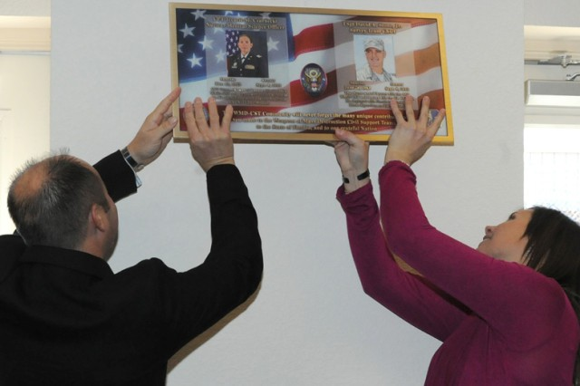 Kevin McNaught and Katie Stone hang a plaque honoring Capt. Tecarie Czarnecki and Tech. Sgt. David Stone Jr. in the Communication and Scientific Laboratory on Jan. 21. Czarnecki and Stone, Civil Support Team members who trained at Fort Leonard Wood, were killed rendering aid to a vehicle crash victim.