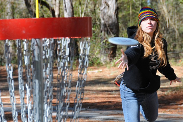 Stephanie Woodard, civilian participant and advanced female winner, tosses a disc at one of the baskets on the disc golf course during the Winter Fling Disc Golf Tournament Jan. 24 at Beaver Lake.