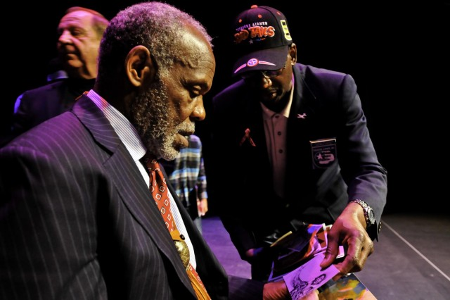 Actor, producer and humanitarian Danny Glover (left) is shown a photo of a Tuskegee Airman by Tayarji Peterson (right) following the concluding comment from Glover during the Honoring the Past and Embracing the Future, an American history tribute to the Buffalo Soldiers at Tacoma, Wash., Jan. 25.