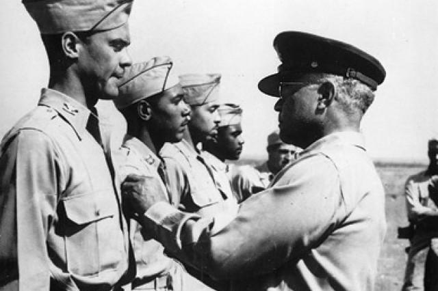 Tuskegee Airman Col. Benjamin O. Davis Jr., left, receives the Distinguished Flying Cross from his father, Brig. Gen. Benjamin O. Davis Sr., at Ramitelli Airfield in Italy, September 1944. Benjamin Davis Sr. was the first black general to serve in the U.S. Army and his son became the first black general to serve in the U.S. Air Force.