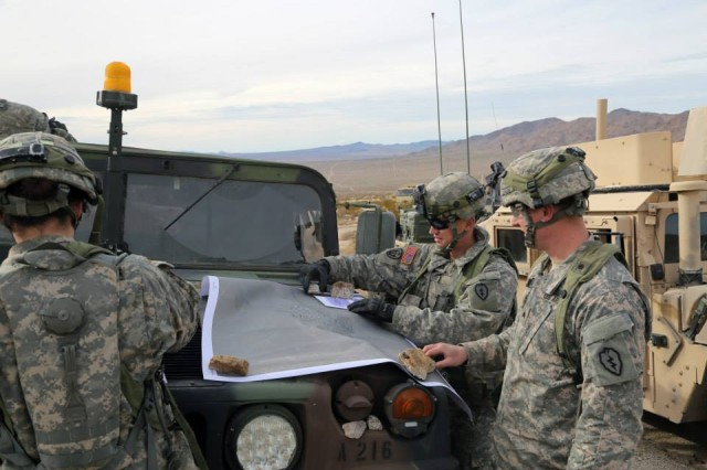 Soldiers, with the 1st Battalion, 5th Infantry Regiment, 1st Stryker Brigade Combat Team, 25th Infantry Division, conduct an area analysis using a map during Decisive Action Rotation 15-03 at the National Training Center at Fort Irwin, Calif., Jan. 28, 2015.