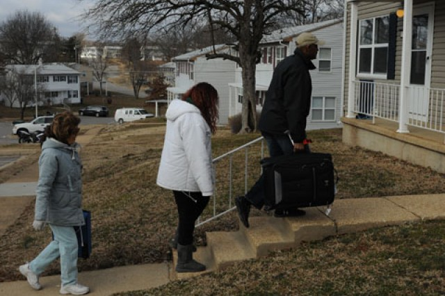 Retiree Randy Cheniault, with his wife, Amy, and daughter Jamie, carry some of their belongings into their new home on post Monday.