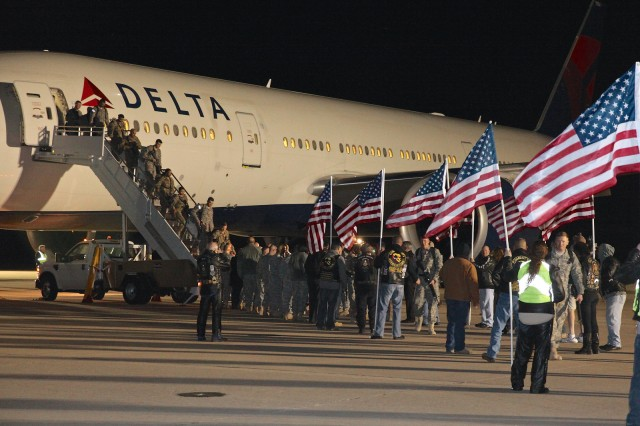Members of the 40th Expeditionary Signal Battalion are greeted by senior leaders shortly after 10 p.m. Wednesday as they arrive at Fort Huachuca's Libby Army Airfield after a nine-month deployment supporting communications contingency operations in support of Operations Enduring Freedom, Inherent Resolve and Spartan Shield in southwest Asia. After shaking hands with a number of people, the 257 arriving Soldiers made their way through a pathway of American flags held by bikers, who have been at every deployment from the fort in recent years, as well as at the events welcoming them back.