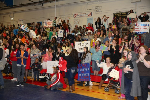 Friends and family cheer as members of the 40th Expeditionary Signal Battalion arrive at Barnes Field House Wednesday. After nine months, only a few moments stand between the returning Soldiers and their families.