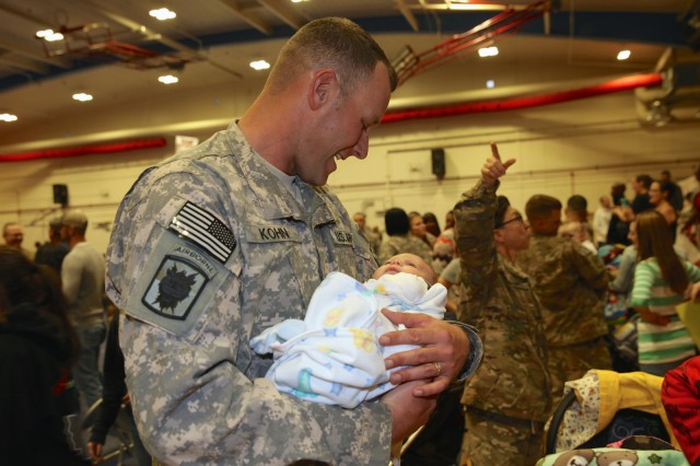 Sgt. 1st Class Mathew Kohn, 40th Expeditionary Signal Battalion, beams with joy as he holds his 2-month-old baby Liam for the first time, Wednesday, at Barnes Field House. Kohn just returned from a nine-month deployment supporting Operations Enduring Freedom, Inherent Resolve and Spartan Shield in southwest Asia.