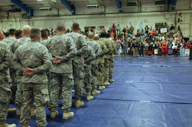"Members of the 40th Expeditionary Signal Battalion stand in formation after returning from deployment. Following a short ceremony they would wait for the order, ""release your units to their families,"" which would officially complete the trip home."