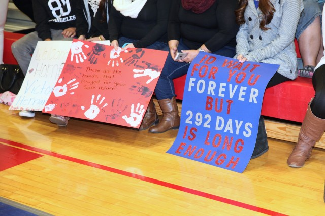 Family members from the 40th Expeditionary Signal Battalion hold signs at Barnes Field House as they eagerly await the return of their Soldiers. The crowd waited for a period of time while the Soldiers completed some in-processing actions at Libby Army Airfield before being bused to Barnes Field House where they were reunited with their families.