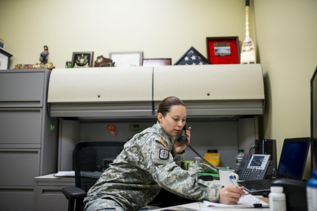 First Sgt. Raquel Steckman, Army Reserve first sergeant for the 374th Engineer Company (Sapper), Concord, Calif., takes a phone call to discuss a Soldier who wants to join her unit. Steckman is the first woman in the Army appointed to a sapper company as a first sergeant. On the shelf above her are various coins, awards and plaques she collected in her various units throughout her Army career. (U.S. Army photo by Sgt. 1st Class Michel Sauret)
