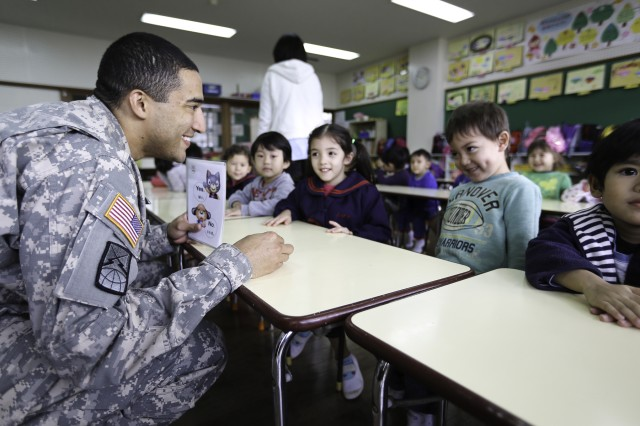 1st Lt. KiAndre Chambers, 349th Signal Company speaks with children at the Kobato Preschool in Yomitan Village Feb. 9. Chambers and other Soldiers regularly volunteer to teach English at the school.