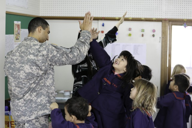 Students at the Kobato Preschool in Yomitan Village exchange high fives with 1st Lt. KiAndre Chambers, 349th Signal Company during an English class Feb. 9.
