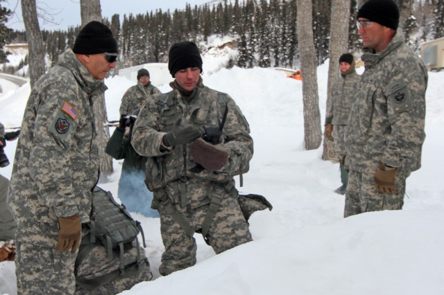 Lt. Dan Sweeney, middle, with 1st Battalion, 52nd Aviation, demonstrates to Army Chief of Staff Gen. Ray Odierno, left, and Maj. Gen. Michael Shields, right, U.S. Army Alaska commanding general, how to call for assistance when in the mountains of Alaska.