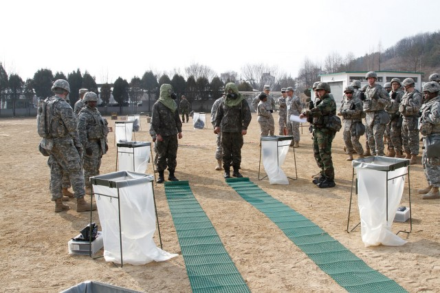Soldiers, of the 293rd Signal Company, 36th Signal Battalion, 1st Signal Brigade, and Soldiers, of the 50th Infantry Division, Republic of Korea Army, discuss the decontamination process during a combined exercise at Base 50, Daegu, South Korea, Feb. 5, 2015.