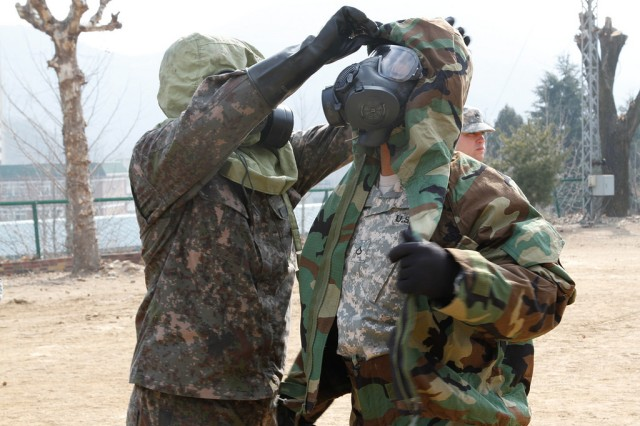 A Soldier, from 293rd Signal Company, 36th Signal Battalion, 1st Signal Brigade, receives assistance removing gear from a member of the 50th Infantry Division, R.O.K. Army, Chemical, Biological, Radiological, and Nuclear explosives team during the combined decontamination exercise at Base 50, Daegu, South Korea, Feb. 5, 2015.