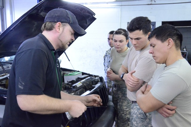 Alex Quick (far left), North Side Auto Skills instructor, shows Spc. Robert Orellano, 3rd Battalion, 320th Field Artillery, 3rd Brigade Combat Team, 101st Airborne Division; Spc. Alison Abey, Better Opportunities for Single Soldiers vice president; Spc. Travis Braud, 5th Special Forces Group, 101st Abn. Div.; and Staff Sgt. Gabriel Ochoa, 5th Special Forces Group, 101st Abn. Div., the importance of checking the color and smell of engine oil to during the BOSS Life Skills Training event, Monday.