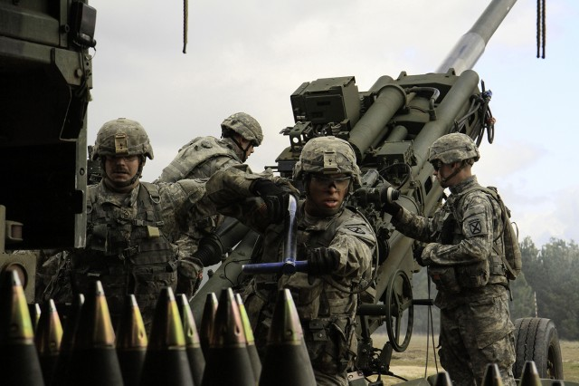 Pfc. Izaac Horton, front, and Pfc. Christopher Roberts, left, both of C Battery, 2nd Battalion, 15th Field Artillery Regiment, 2nd Brigade Combat Team, reset after ramming a 155 mm high-explosive round into the breach of a M777 howitzer Feb. 8 on Peason Ridge, Fort Polk, La. Ramming the round into the breach allows room for the powder charge to be inserted.
