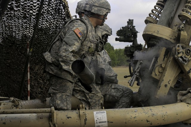 Spc. Jesus Manzanerez, artilleryman with B Battery, 2nd Battalion, 15th Field Artillery Regiment, ejects a 105 mm shell casing from the M119 howitzer during live-fire crew drills.