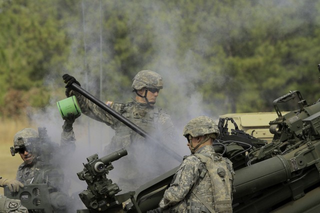 Spc. Robert Cragg, cannoneer with C Battery, 2nd Battalion, 15th Field Artillery Regiment, swabs the breach of the M777 howitzer during a fire mission. Swabbing the breach between each round fired minimizes residue buildup that can affect accuracy or catch fire resulting in premature detonation of the round.