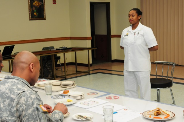 Pvt. Peauline Wellsevans from 2nd Battalion, 1st Air Defense Artillery Regiment, explains a dish she prepared to the board members at the Eighth Army Chef of the Quarter board Feb. 12 at Sungnam, South Korea.