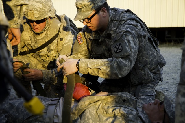 Pvt. Jared Morin (right), a combat medic assigned to Hellcat Company, Headquarters and Headquarters Troop, 1st Squadron, 89th Calvary Regiment, 2nd Brigade Combat Team, assists in securing a notional patient to a stretcher during a mass casualty scenario Feb. 11 at Joint Readiness Training Center, Fort Polk, La. To hone their quick reaction to a base wide emergency, all medical personal from combat medic, to aid station medics to the battalion doctor participate in the event. (Photo by: Staff Sgt. Jennifer Bunn)