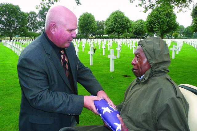 Netherlands American Cemetery Superintendent Mike Yasenchak presents the U.S. flag to veteran Jefferson Wiggins for his role in helping to bury thousands of U.S. Service members there during World War II. The flag had been flown over the cemetery in his honor.