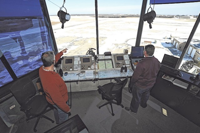 Air traffic controllers Allen Moll, left, and Bill Urena observe a plane landing at Forney Airfield on Fort Leonard Wood.
