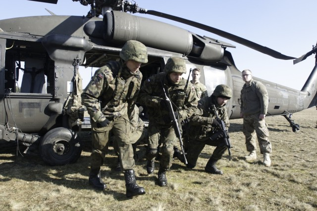 "Polish infantrymen, from 3rd Company, 1st Infantry Battalion, 12th Mechanized Brigade, egress from a UH-60 ""Black Hawk"" during medical evacuation training at the Drawsko Pomorski Land Forces Training Center, Feb. 26, 2015."
