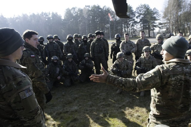 Spc. Joseph Sylvester, right, crew chief for B Company, 3rd Battalion, 158th Assault Helicopter Brigade, conducts a pre-flight safety briefing to U.S. and Polish ground forces at Drawsko Pomorski Land Forces Training Center, Feb. 26, 2015.