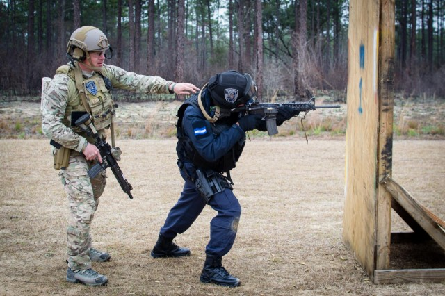 A Green Beret, left, assigned to the 7th Special Forces Group (Airborne), guides a member of the Honduran Tigres during a shooting drill requiring him to engage targets from behind an obstacle on an Eglin Air Force Base range, Feb. 24, 2015.