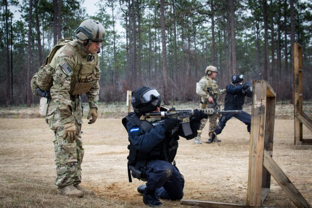 Green Berets, assigned to the 7th Special Forces Group (Airborne), guide members of the Honduran Tigres during a shooting drill requiring them to engage targets from behind an obstacle at an Eglin Air Force Base range, Feb. 24, 2015.