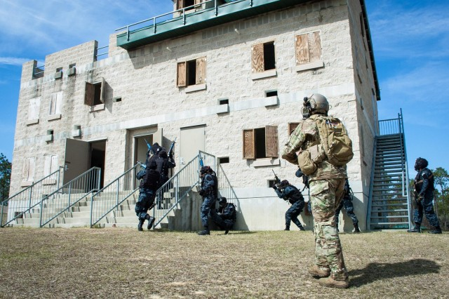A Green Beret, from the 7th Special Forces Group (Airborne), observes Honduran Tigres as they assault a building that serves as their objective on an Eglin Air Force Base range, Feb. 27, 2015. The Tigres, a counter-narcotic and counter-trafficking force, were participating in culmination exercise testing.