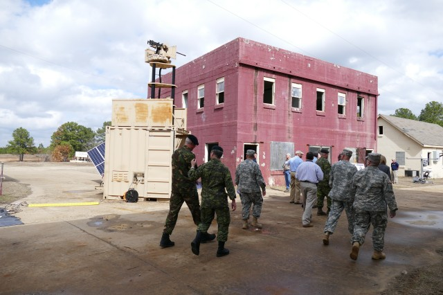 Visitors to the Army Expeditionary Warfighter Experience walk by the Containerized Weapons System March 3, 2015. The Containerized Weapons System was designed to provide enhanced lethality and bolster force protection.